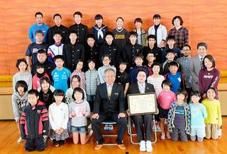 第17回環境美化教育優良校等表彰の優良校に選ばれた名蔵小中学校の児童生徒ら=8日午前、名蔵小体育館