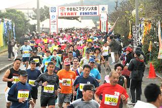 第24回竹富町やまねこマラソン大会。603人の出走者全員が完走を果たした10㌔部門で、号砲とともにコースに駆け出すランナーたち=11日午後、上原小学校校門前