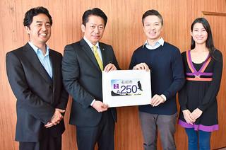 石垣市ご当地ナンバープレートのデザインを発表した選考委員会の平田睦事務局長、中山義隆石垣市長、デザインしたコウ・ジャッキーさんと妻のコウ・和佳奈さん(左から)