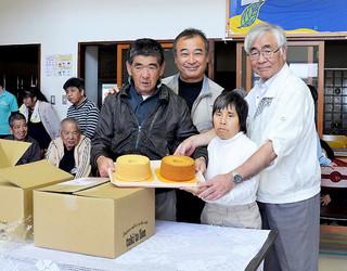 大澤邦昭氏(右)とともにシフォンケーキの贈呈を喜ぶ利用者ら=16日午後、育成園玄関ホール