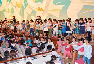 くにぶん木の会のメンバーと一緒に「ドキドキドン!1年生」を歌う子どもたち=19日午後、市民会館大ホール