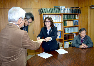 大得英信教育部長(左)に要望書を手渡す田本由美子元委員長(中央)ら=21日午前、市教委