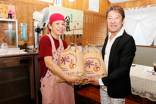 川満牧子さん(右)に米10㌔を手渡す今西敦之代表=23日午後、のりば食堂