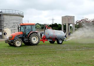 テストプラントで生産された有機液肥の散布試験。トラクターにけん引されたバキューム車から散布される=6日夕、石垣市し尿処理場