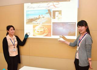 平田観光の新たなツアー商品を担当者に提案する実習生で麗澤大学の齋藤彩花さんと堀文美さん(右から)=7日午後、同社