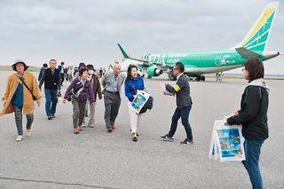 FDAのチャーター便で来島し、町と町観光協会の関係者から歓迎を受ける長野からのツアー客=8日午後、与那国空港