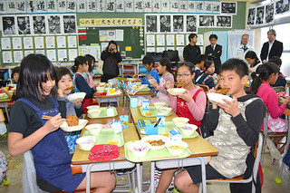 八重山産もずくと石垣島産のにんじんを使ったかき揚げをほおばる石垣小学校の5年生たち=10日午後、同校