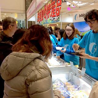 香港で初めて行われた「石垣島観光物産フェア」で市の特産品を来場者に販売する関係者(奥)=11日午後、香港九龍(市商工振興課提供)