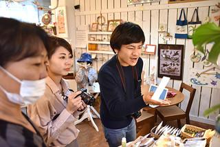 ユーグレナモール内の雑貨店「ひらりよ商店」で取材するメディアツアーの参加者=15日午後、同店