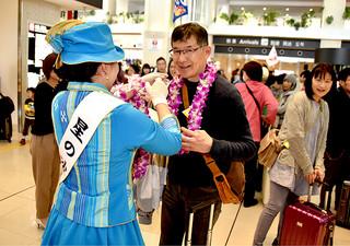 ミス八重山の新里諒さんから花輪のレイを掛けられて喜ぶFMヨコハマリスナーツアーの参加者=17日午後、南ぬ島石垣空港