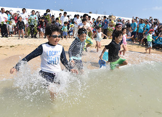 オープニングテープカット後の初泳ぎで、勢いよく真っ青な海に飛び込む子どもたち=18日午前、小浜島、はいむるぶしビーチ