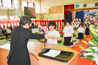 登野城小学校の卒業式で、浦崎喬校長(左)から笑顔で卒業証書を受け取る卒業生=23日午前、同校体育館