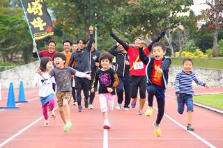 みんなの陸上競技石垣島ゆいまーるリレーマラソン&ウォークに参加する人たち。子どもたちも楽しそう=3月26日、石垣市中央運動公園陸上競技場(みんなの陸上競技実行委員会提供)