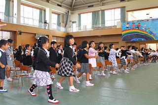 平真小学校に入学した新1年生。曲に合わせて踊りを披露する=10日午前、体育館