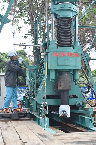 専用の機械を使って温泉掘削を始める工事関係者=11日午後、竹富島