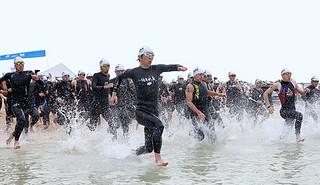 波しぶきを上げ海に入っていく選手ら=16日午前、南ぬ浜人工ビーチ