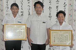 遊泳中に沖へ流された小学生3人を救助したとして中山義隆市長から感謝状を受けた小島葉子さん(左)と松浦七海さん(右)=18日午後、石垣市役所市長室