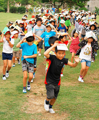 駆け足で避難する平真小の児童ら=23日午前、石垣市中央運動公園内