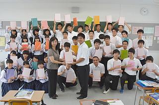 学校全体で勉強を頑張る空気をつくろうと真久田絹代校長(中央左)が直接手渡している自学自習ノートを手に、笑顔の八重高1年2組の生徒たち=25日午前、同校