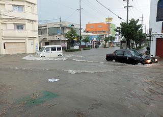 市役所前の通りも冠水、川と化した=26日午前8時15分ごろ、いずみスーパー前交差点