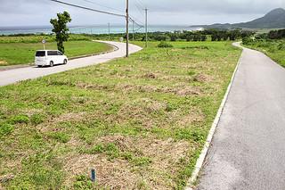 新出張所の移設先。道路に挟まれた中央の草地部分に建設が予定されている=8日午後、伊原間