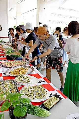 県産品のゴーヤを試食する観光客ら=8日午前、同ゆらてぃく市場