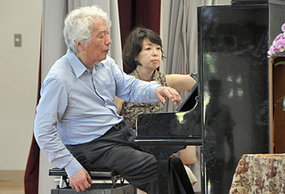 左手によるピアノ演奏で美しい旋律を披露した舘野泉さん(手前)=11日午後、竹富小中学校体育館