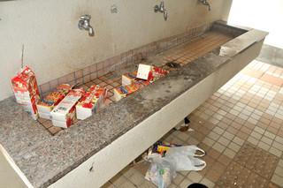 ごみのポイ捨てが常態化している真栄里公園。西口トイレの手洗い場には紙パックなどが散乱していた=15日午前