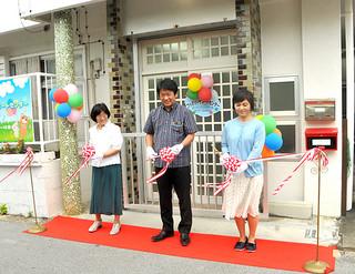 石垣市ファミリーサポートセンターの新拠点の開所を喜び、テープカットを行う関係者たち=15日午前、登野城