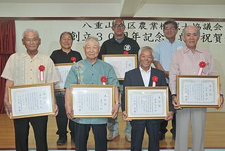 八重山地区農業機械士協議会の創立30周年記念式典で表彰状を手渡された受賞者ら=16日夜、北京飯店