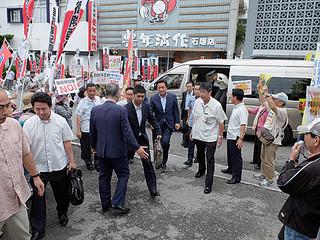 反対派と推進派ののぼり旗が乱立する中、市役所に向かう若宮健嗣防衛副大臣(中央)=17日午後、市役所玄関前