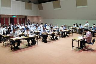 第53回石垣島まつりの開催要項などについて説明を受ける委員ら=25日午後、市民会館中ホール