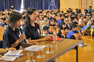 平和学習でまつぼっくりの会が読み聞かせを行った=19日午前、宮良小学校体育館