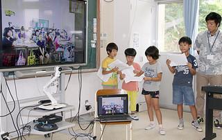 テレビ電話を通して、八重山と沖縄本島の戦争体験を紹介し合う児童ら=20日午後、大本小学校