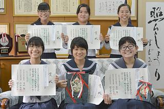 第64回NHK杯全国高校放送コンテスト県大会で最優秀賞を受賞した新垣春菜さん(前列中央)と優秀賞を受賞した輕部あいりさん(同右)、優良賞を獲得した皆さん=21日午後、八重高校長室