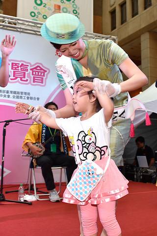 特設ステージで行われたモーヤーで、台湾の子どもと一緒に踊るミス南十字星の大久奈織さん=24日午後、台湾・台北市の台北駅