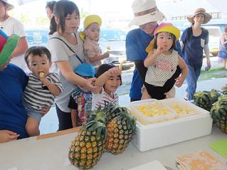 旬入りしたハワイ種の試食に大喜びの子どもたち=1日午前、JAファーマーズマーケットゆらてぃく市場