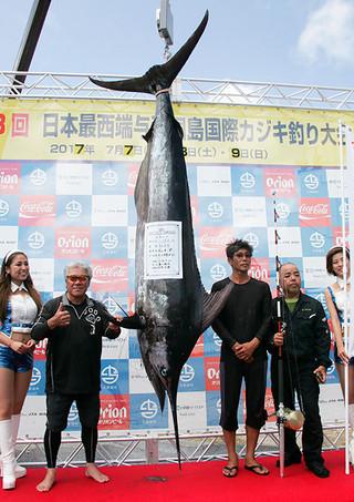 この日最大の162㌔のクロカワカジキを釣り上げたチーム世美がえりの当山喜一郎さん(左3人目)=8日、久部良漁港