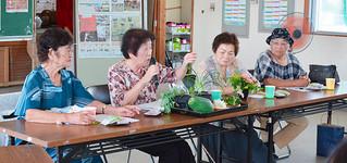 「スーマカシ」で使用する材料などを紹介する波照間紀代子さん(左から2人目)ら=9日午後、新川公民館