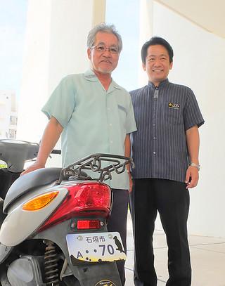 中山義隆市長(右)から「石垣市A・・70」の記念ナンバープレートの交付を受け、原付バイクに取り付けてもらった波平吉次さん=10日午前、市役所ピロティ
