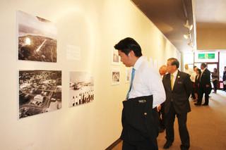 写真を見ながら70年の歴史に思いをはせる関係者ら=10日、石垣市民会館展示ホール