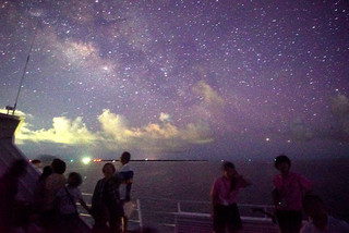 洋上星空観察ツアーを楽しむ参加者らと八重山商工高校商業科観光コースの生徒ら=12日夜、竹富島沖の洋上(八重山星の会通事安夫代表理事提供)
