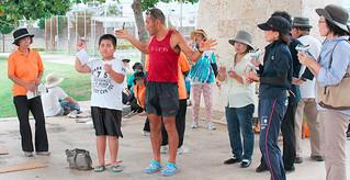 紙飛行機の飛ばし方のこつを教わる参加者ら=16日午後、真栄里公園