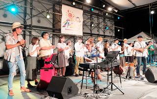 「島人ぬ宝」を楽しそうに歌うBEGINのメンバーと石垣中2年2組の元生徒ら=16日夜、新栄公園
