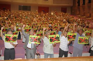 「ミサイル」「基地」の文字に大きくバツ印を付けたプラカードを掲げ、配備反対を訴える参加者ら=22日夜、石垣市民会館大ホール