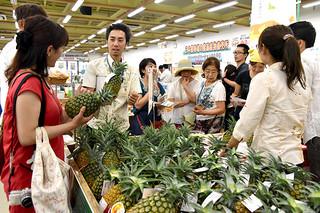 県が展開した販促活動で、果汁糖度19度以上の新品種パインアップル「サンドルチェ」を買い求める観光客ら=24日午後、JAゆらてぃく市場