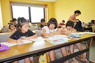 夏休みの宿題など学習に取り組む子どもたち=1日午前、市立図書館