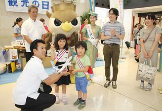 1日の2017人目の来島者となった田嶋範之さん家族4人(中央)=1日午後、南ぬ島石垣空港