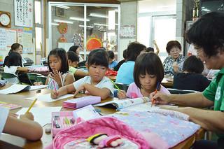 夏休み子ども居場所づくり・学習会で夏休みの宿題などに励む子どもたち=2日午前、新栄町公民館