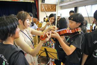 東北ユースの楽団員(左から2人)からバイオリンの手ほどきを受けるマーチングバンド部の部員=9日午前、県立石垣青少年の家体育館